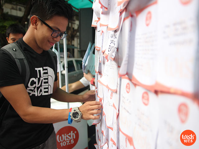 A TUPian posts a wish note on the Wishing Wall.