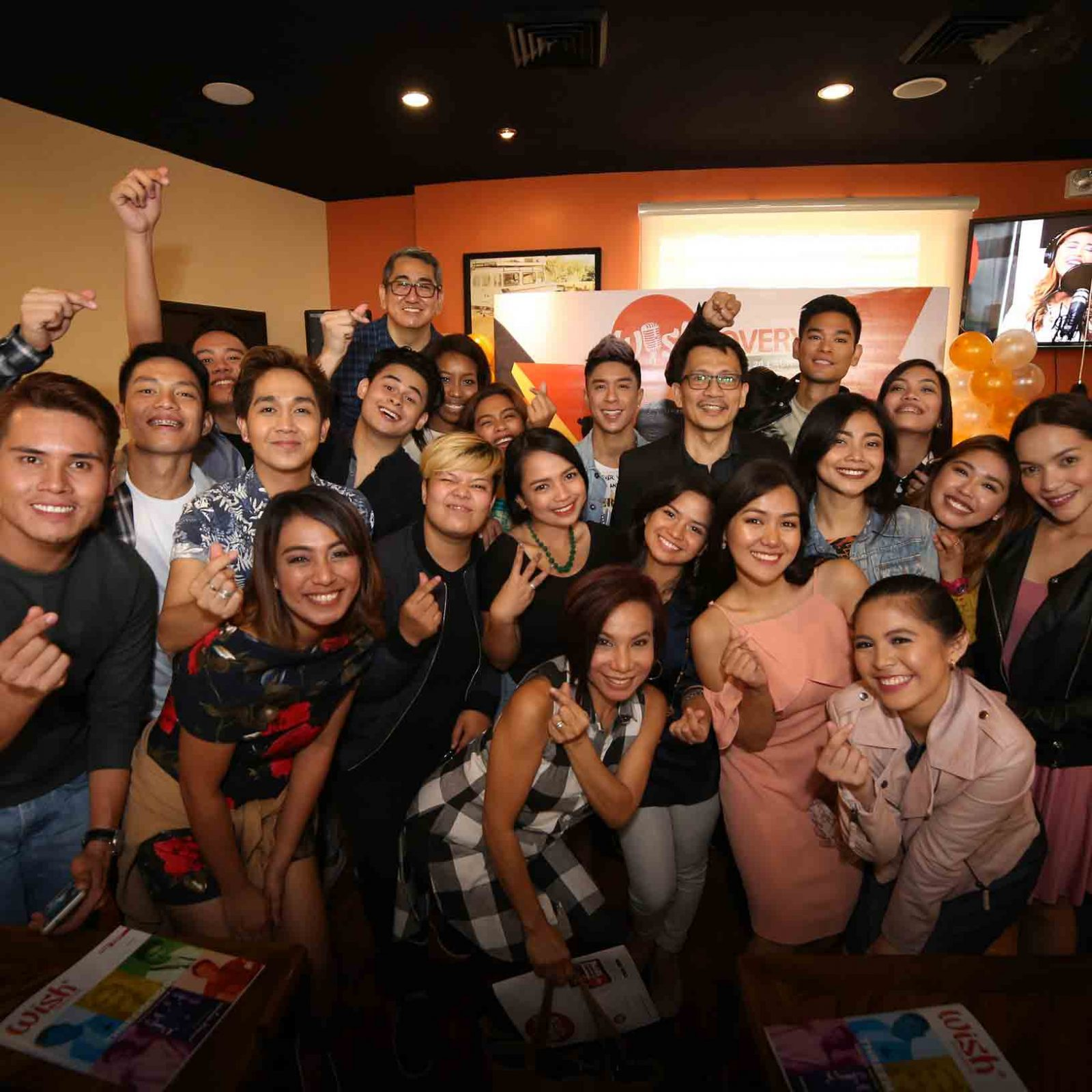 Wishcovery's Wishful 20 — the top 20 finalists of the biggest and freshest online singing competition in the country — pose for a fun photo with the Wishcovery reactors, host, and Kuya Daniel Razon.   (Photo courtesy of Photoville International)