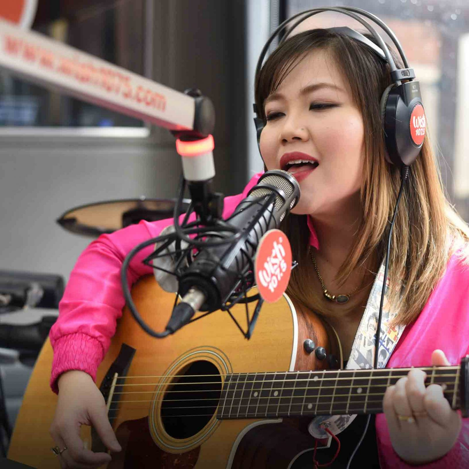 "Singing sweetheart Sabrina performs her acoustic take on ""Versace on the Floor"" and ""Something Just Like This"" live on the Wish Bus.   (Photo courtesy of Photoville International)"