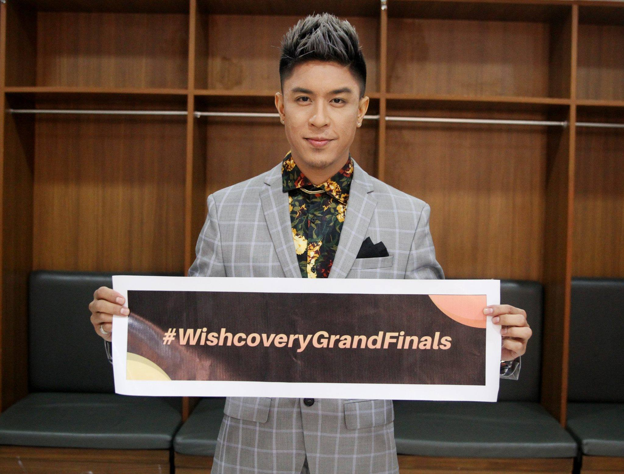 Holding the event's official hashtag is Wishcovery's debonair host Kris Lawrence. #WishcoveryGrandFinals
