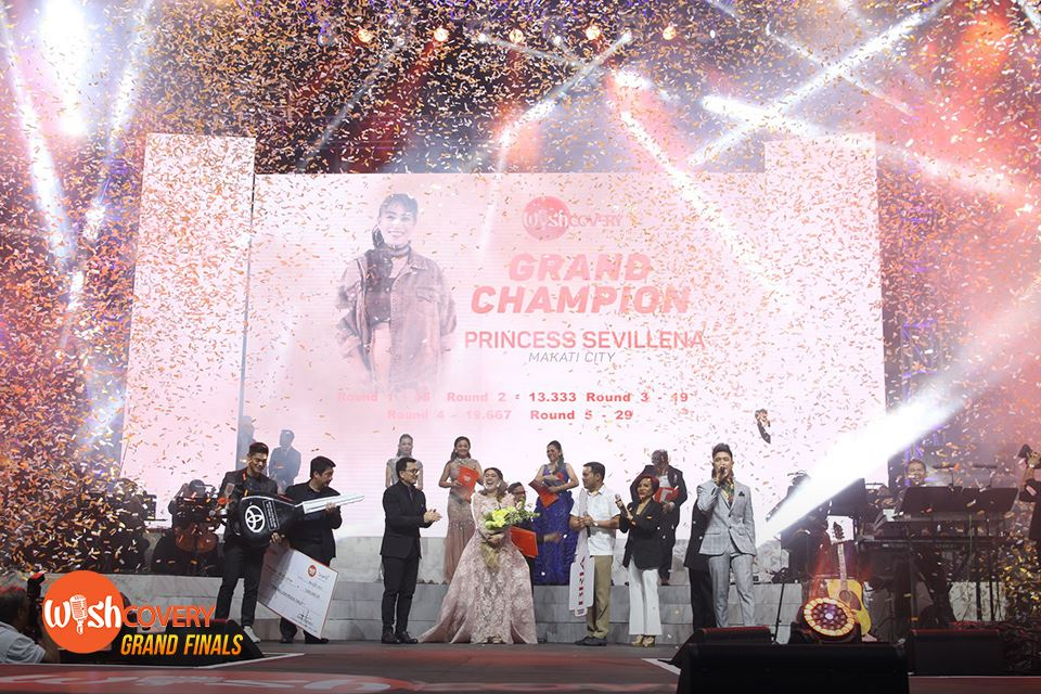 Confetti rained down on the Wishcovery stage as BMPI President and CEO Kuya Daniel Razon (center left) and other BMPI executives gather around Wishful Princess Sevillena to present her award and prizes.